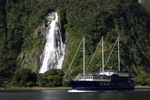 Bowen Falls and a tourist boat in Milford Sound